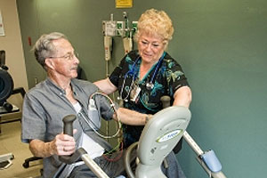 nurse helping elderly man on a stationary bike
