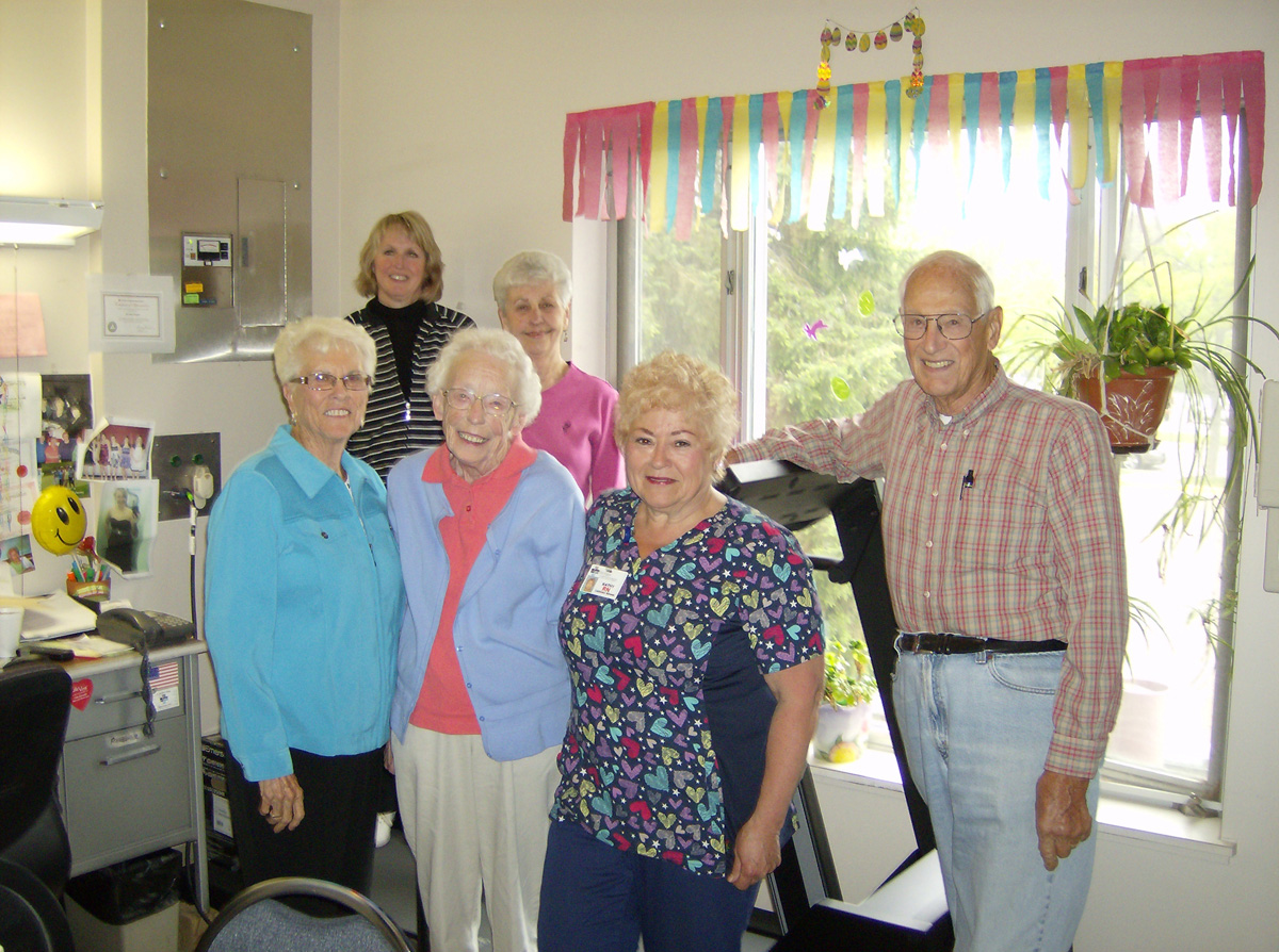 foundation members posting with treadmill in cardiac rehab purchased through foundation