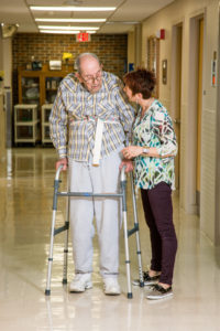 female nurse helping elderly male patient with a walker