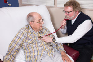 male doctor using stethoscope on elderly male patient